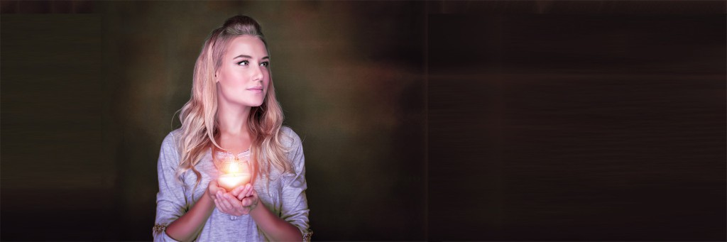 Portrait of beautiful blond girl with glowing candle in hands on